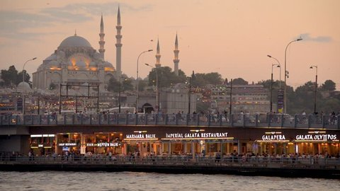 ISTANBUL, TURKEY, AUGUST 3, 2018: Sunset view and lights of Galata Bridge, a bridge that spans the Golden Horn in Istanbul, Turkey. Suleymaniye Mosque can be seen at the background.