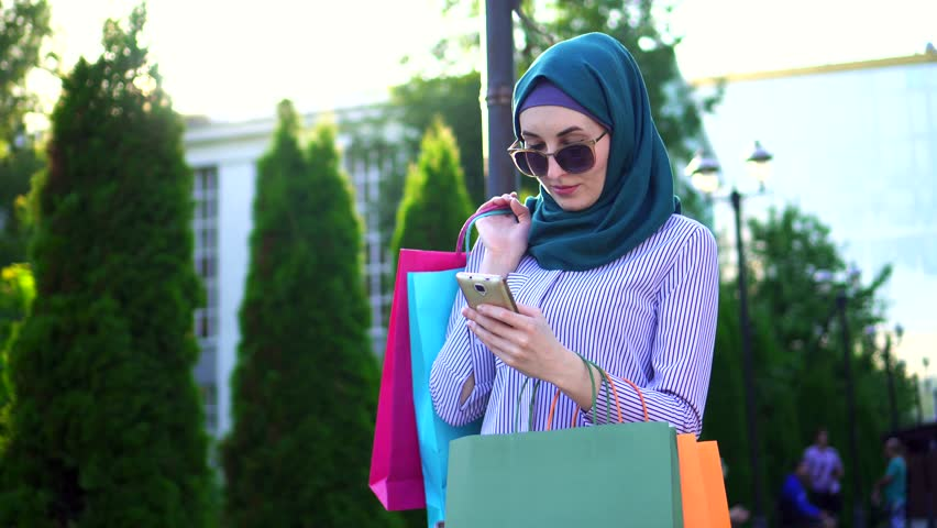 Young muslim woman in hijab bags in his hands after shopping using the phone.Sunflare
