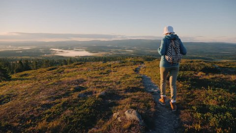 A woman traveler with a backpack behind her back walks through the picturesque highlands in Norway