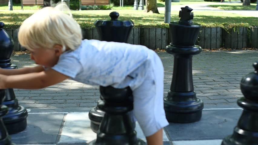 Large chess outdoors with 1.5 years cute boy inside panoramic shot