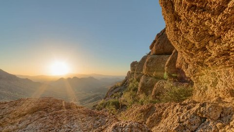Timelapse of a desert sunrise viewed from a mountain pass.  Shot in HDR.  Includes hyperlapse sliding motion past rocks in the foreground.