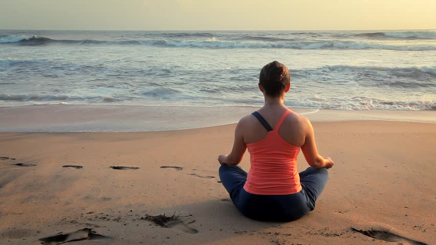 Woman doing yoga - meditate and relax in Padmasana Lotus asana pose with chin mudra outdoors at tropical beach on sunset | Shutterstock HD Video #1014633587