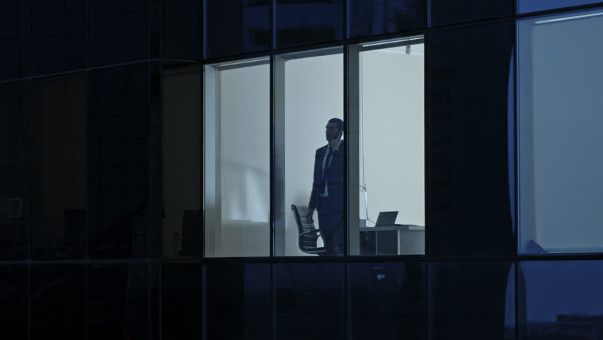 Aerial View Footage: From Outside into Office Building with Businessman Using Mobile Phone and Standing by the Office Window. Beautiful Flying Shot of The Financial Business District Skyscrapers.