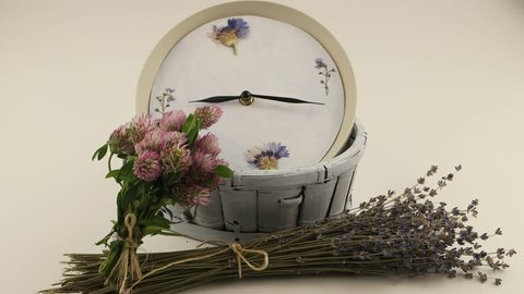 Clock in the pale blue wicker basket and bouquets of   the dry lavender flowers and the clover flowers against a white background, a floral composition