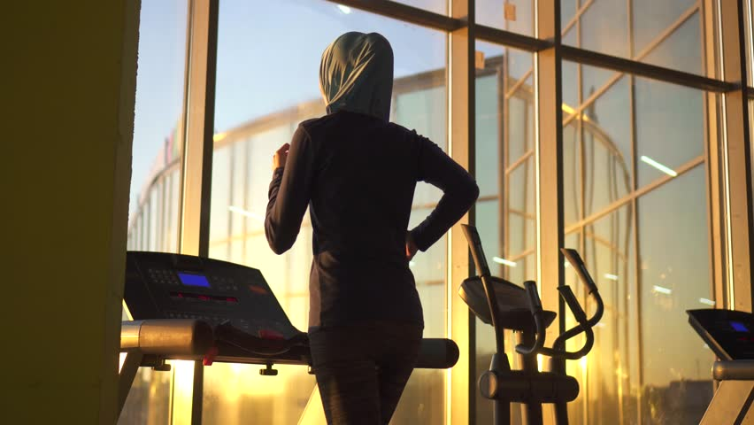 Young sporty muslim girl in hijab doing on the treadmill.Sunflare | Shutterstock HD Video #1014689897