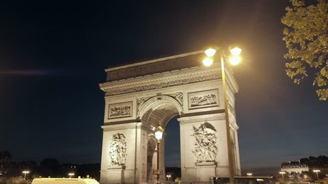 Night forward tracking right view of Arc de Triomphe over sidewalk through trees to roundabout edge at Place Charles De Gaulle in Paris, France