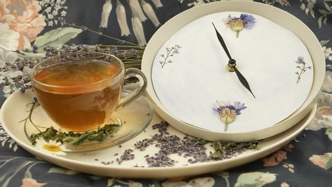 The cup of herbal tea on a white dish. A clock and a bouquet of dry lavender against a background of fabric with a floral pattern, a tradition of 5 o'clock tea
