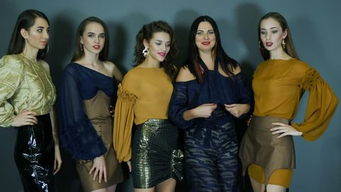 group of models in chic clothes with expressive makeup posing in the studio, stylish photo shoot