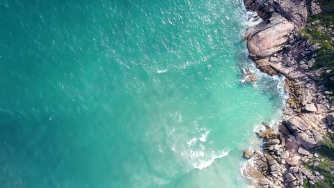 amazing aerial view azure ocean waves swash gently against rocky shore in Vietnamese tropics