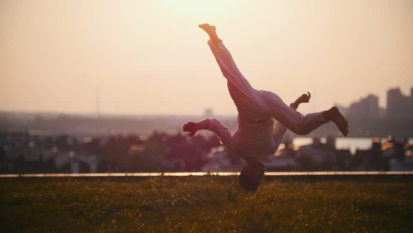 Strong man physically demonstrates very cool tricks on the grass against the background of a pink sunset | Shutterstock HD Video #1014739907