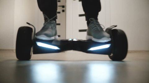 Close-up low angle shot of male legs in sneakers moving around on gyro scooter in apartment with white walls and doors