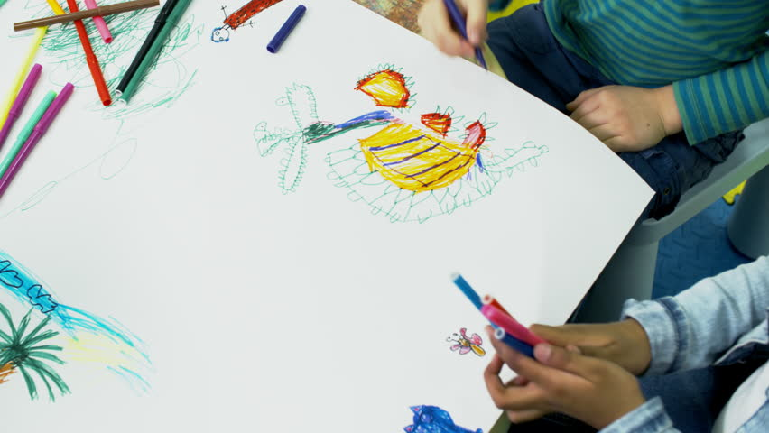 Tracking shot of children of primary school age using colored felt tip pens when drawing pictures on big sheet of paper, above view | Shutterstock HD Video #1014797267