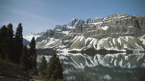 4K Bow lake, Banff, Alberta - Mirror reflections of mountains and trees in foreground - Panning right, wide angle