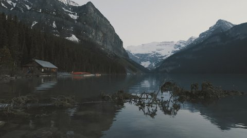 4K Lake Louise, Branch in water, cabin and mountains in background - Banff National Park, Alberta, Canada - wide angle shot, dusk, twilight