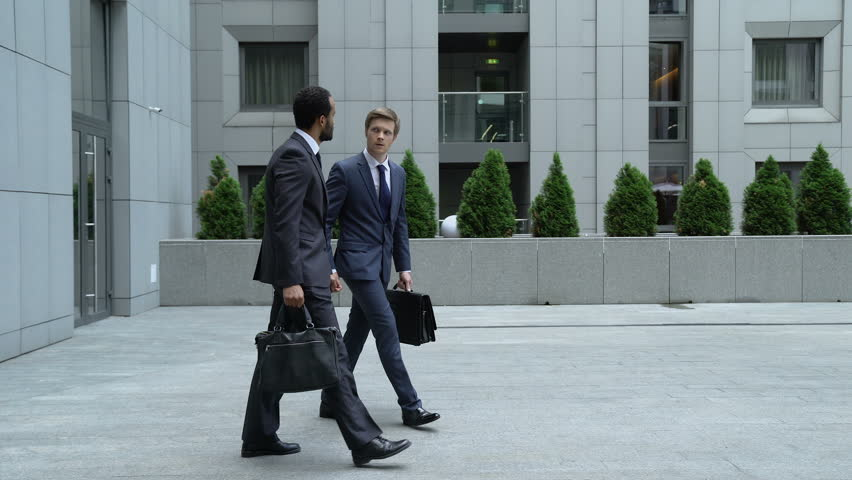 Businessmen talking outdoors, new employee trying to make friends with coworker