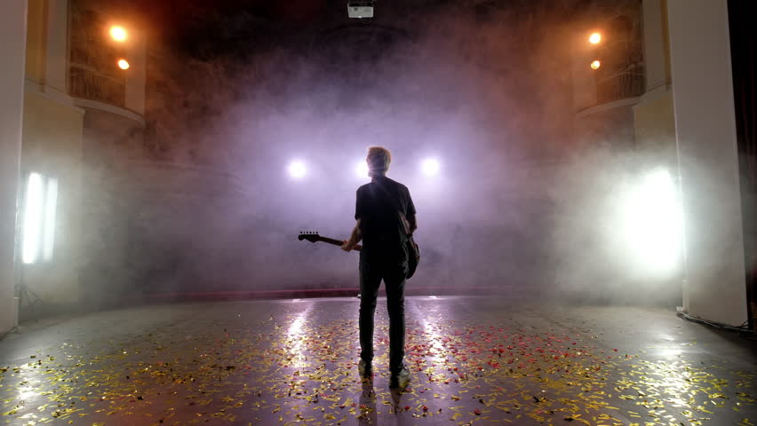 Concert rock band performing on stage with singer guitar. Music video punk, heavy metal or rock group. The guitarist performs on stage. Stage light, smoke. Back view | Shutterstock HD Video #1014861127