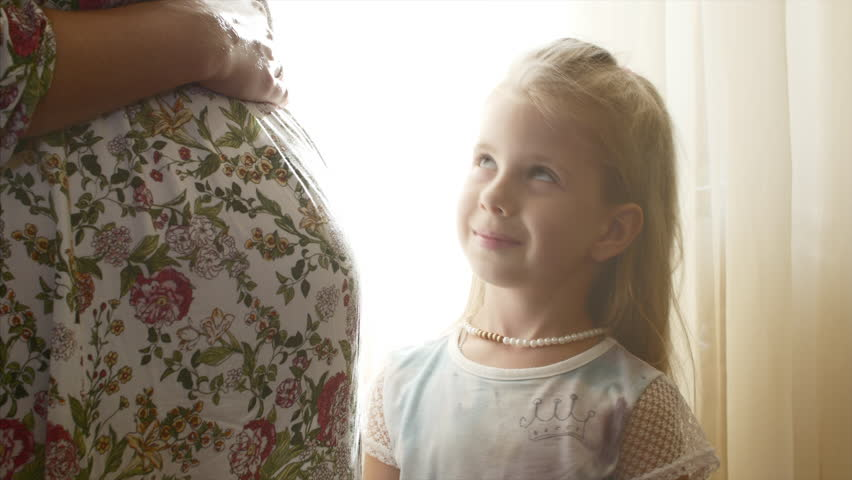 Pregnant mother is beside her daughter, a little daughter looks into her mother's eyes, and then hugs Mom. | Shutterstock HD Video #1014862597