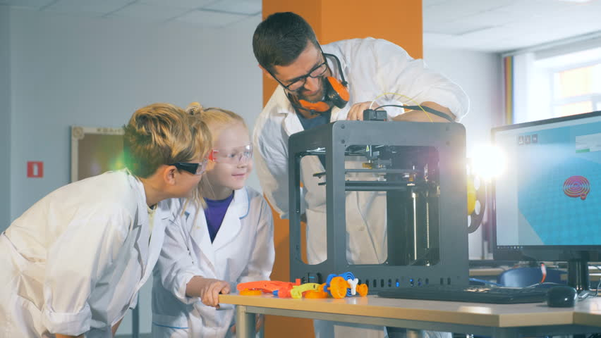 Modern education concept. Chikdren study technology with a engineer in a school lab. | Shutterstock HD Video #1014866587