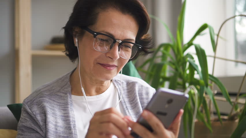 Senior woman in glasses watching videos on her brand-new smartphone at home and touching earphones by her hand. Portrait. Indoors. | Shutterstock HD Video #1014879337