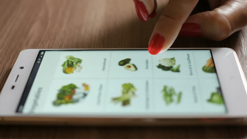 Woman orders food home in an online store using a smartphone. Female selects the vegetables in the grocery online store. Close-up. 4K UHD. Screen is blurred  | Shutterstock HD Video #1014888307