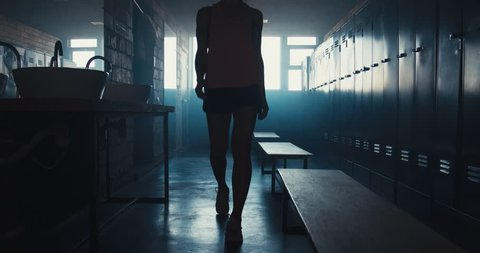 DOLLY IN Caucasian female athlete preparing for a workout in a gym locker room, tying shoelaces before training session. 4K UHD 60 FPS SLOW MOTION