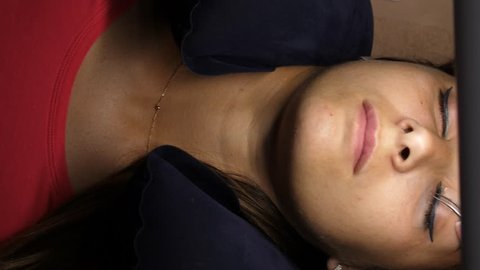 Woman eye with long eyelashes. Eyelash extension. Gluing artificial eyelashes with tweezers. A woman lies under a lamp on a cosmetic procedure. top view, movement of the camera.