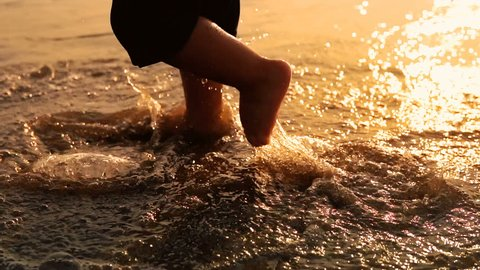Following and undefined baby feet walking on beach at sunset with sea waves splashing his barefoot legs, SLOW MOTION