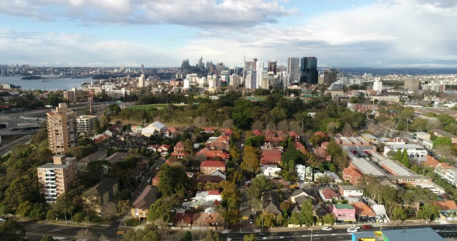 St Leonards park on Sydney Lower North Shore in North Sydney with sports grounds and oval in aerial forward flying over local houses and streets.