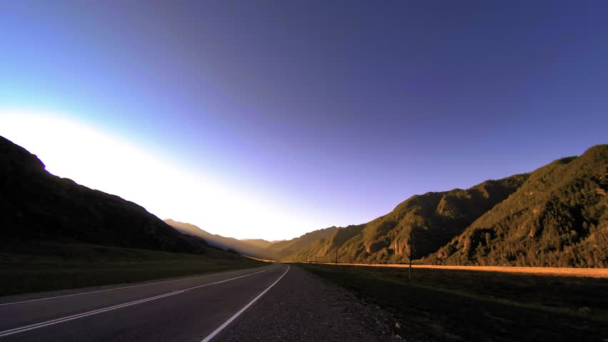 4K UHD mountain road timelapse at the summer or autumn sunset sunrise time. Wild Russian nature and rural field. Green grass field and sun rays movement.