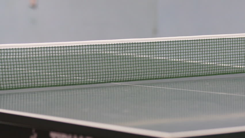 We can see a white ping pong ball travelling from one side of the table to another. Mens are playing table tennis. | Shutterstock HD Video #1014978967