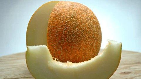 Honeydew melon rotating on a wooden plate. 4K