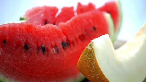 Honeydew fresh melon and watermelon rotating on a wooden plate. 4K