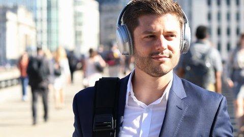 Businessman Wearing Wireless Headphones Walking To Work In Slow Motion
