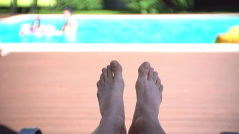 Male legs on daybed by the swimming pool