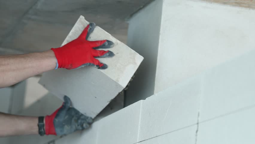 bricklayer builder working with autoclaved aerated concrete blocks. Walling