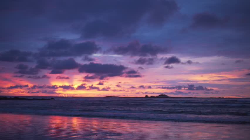 Out of focus background plate of pretty orange, purple and blue sunset on the beach in Costa Rica for compositing or keying. Blurred or defocused shot of ocean sun set for green screen composite. 4k