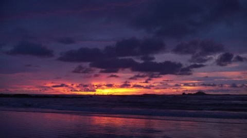 Pretty out of focus background plate of orange, purple and blue sunset on the beach in Costa Rica for compositing or keying. Blurred or defocused shot of ocean sun set for green screen composite. 4k