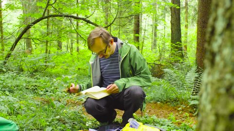 A scientist environmentalist exploring plants in a forest. He examining plant and comparing it with the description in the plant identification book