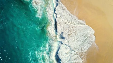 Aerial view waves break on white sand beach. Sea waves on the beautiful beach. drone 4k shot. zoom in