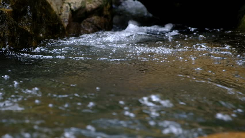 Closeup. The stream flows water with brown rocks.  | Shutterstock HD Video #1015025437