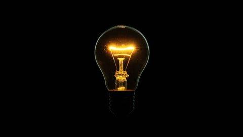 Tungsten light bulb lamp blinking over black background, macro shot