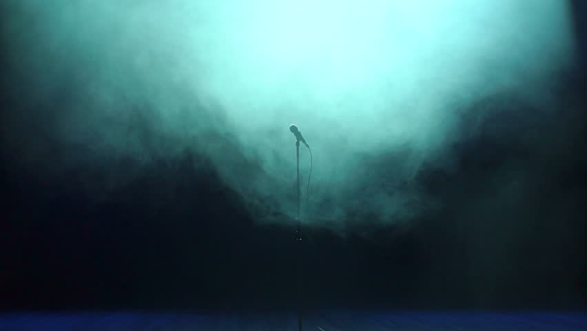 Microphone on stage against a black background with blue lighting. Microphone in a smoke on a dark background. Music instrument concept.