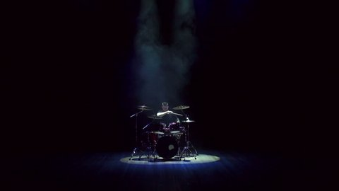 Drummer of a rock band on the stage plays drums during a musical performance, live show, indie rock, pop rock. Man playing drums on black background with smoke. Wide shot.