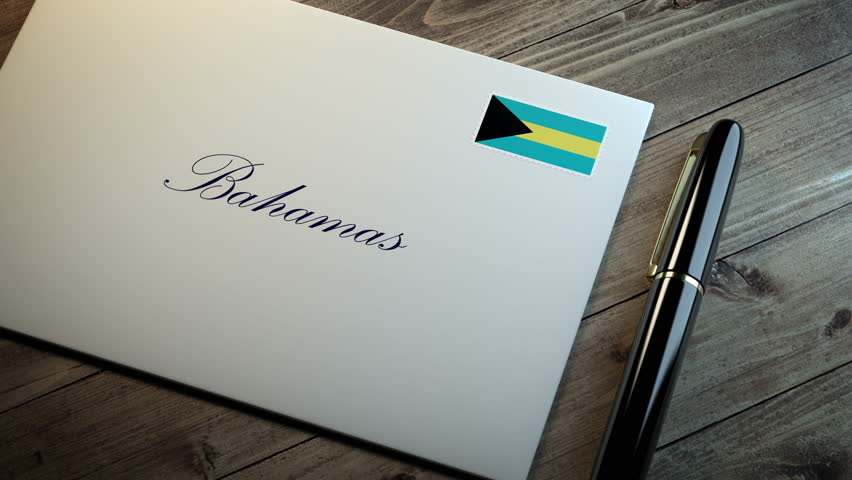 Country name written on a card or envelope in cursive font with a sleek pen on a wooden table surface under beautiful classy light. Stamp in the corner shows the flag of Bahamas