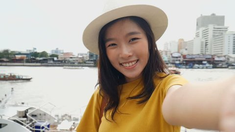 Beautiful asian woman taking selfies on a smartphone. Young asian girl tourist travel to thailand.