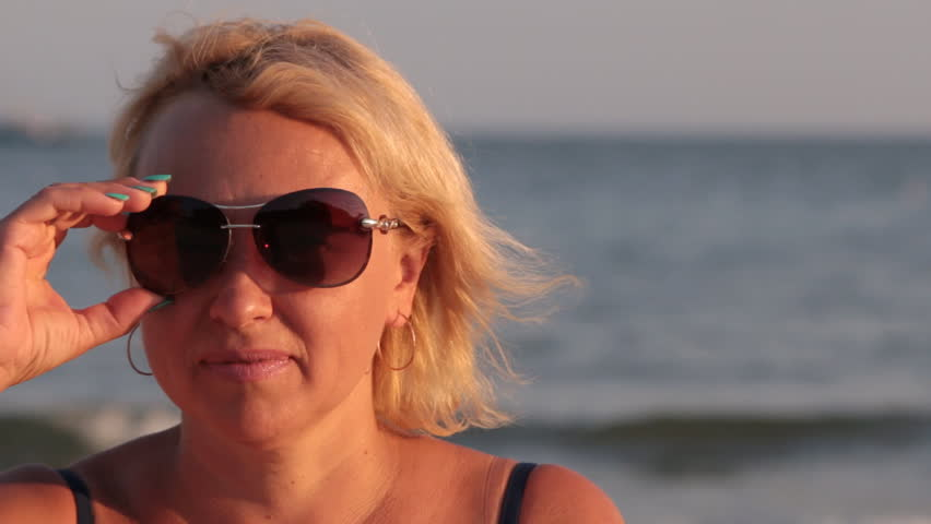 Close-up, a woman takes off sunglasses and looks into the camera.