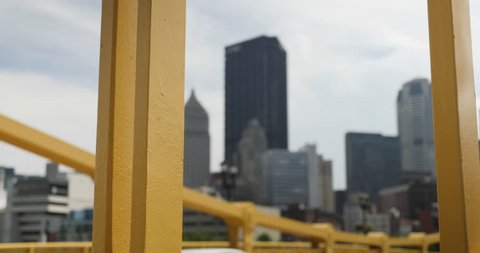 A daytime tracking dolly shot of the Pittsburgh skyline as seen through the yellow steel beams of the Andy Warhol Bridge.