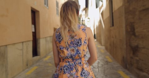 Young Blonde Pretty Woman in a Summer dress Walking through the Spanish Old Town Palma City. Gap Year Girl Student in Europe. Looking around Exploring The City. Looking up at the Old Town Houses.