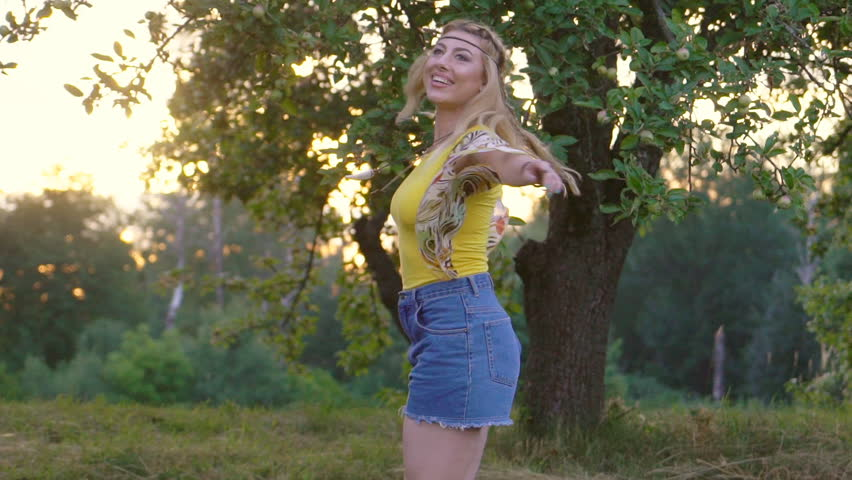 young attractive woman in a yellow T-shirt is spinning at sunset. green apple orchard on background. happy and free hippies