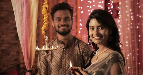 A happy husband and wife in a house interior decorated with lights and flowers. A beautiful woman wearing sari lights a oil lamp during Diwali festival while man wearing Kurta looks on with a smile
